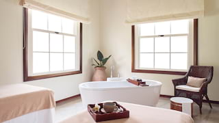 A standalone bathtub in a sunlight filled spa therapy room