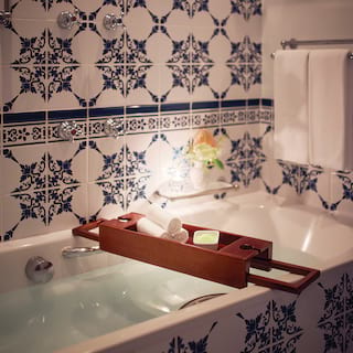 A full, candlelit bath surrounded by blue and white patterned tiles
