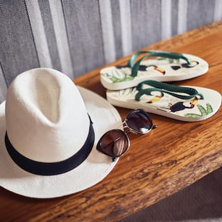 White Panama hat with sunglasses and flip flops on a wooden bench