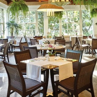 Bright and airy bistro with rattan seating, overlooking lush gardens