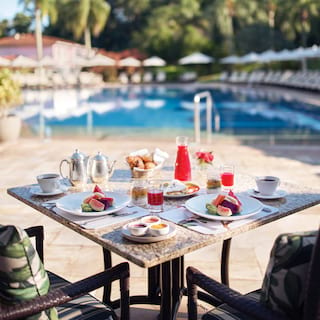 Outdoor table overlooking a hotel pool, laden with fresh fruit dishes