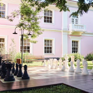 Large outdoor chess set on wooden decking in front of a pink building