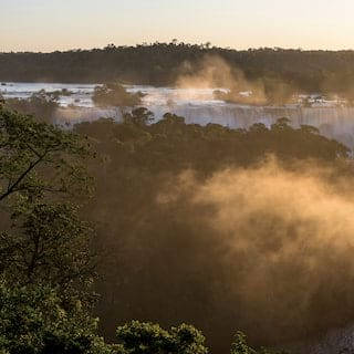 Mist rising from the Iguassu Falls at sunrise