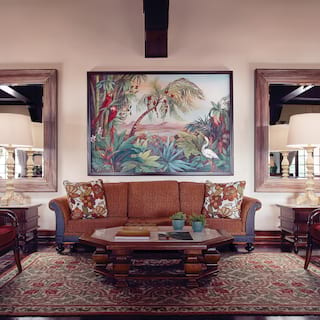 Stylish seating area with brown and red furnishings under a large jungle painting