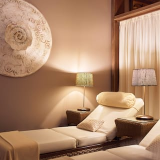 Two spa therapy beds in an elegant lamp-lit room with minimalist decor