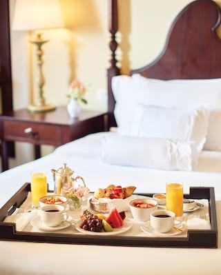 Room-service breakfast tray laden with breakfast dishes placed on a pillowy bed