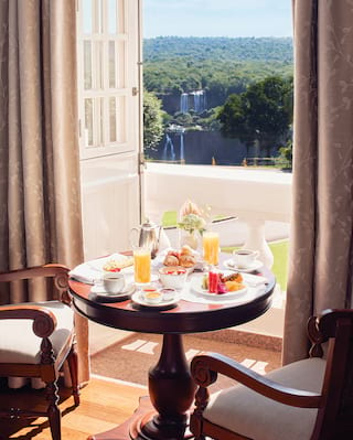 Circular table laden with breakfast dishes next to a sunny balcony