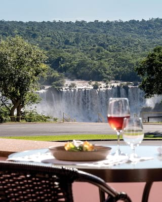 The falls at Iguassu with a filled wine glass on an outdoor table in the foreground
