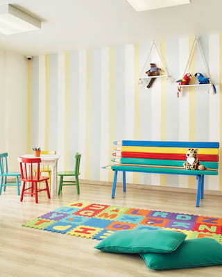 Brightly coloured tables and chairs in a light room filled with kids toys