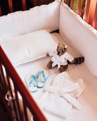 Baby cot containing a small waffle bathrobe, lemur teddy and kids flip flops