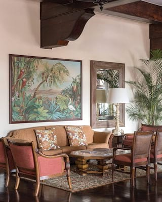 Seating area with fawn and maroon furnishings, under a large jungle painting