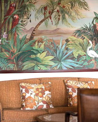 Close-up of a fawn colored sofa and a large painting of a jungle scene