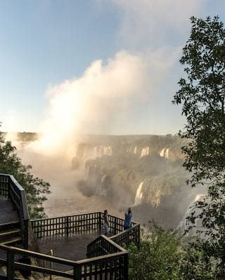 A couple photographing the Iguassu Falls at sunrise