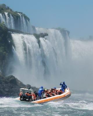An orange speed raft with guests on board approaching the Iguassu Falls