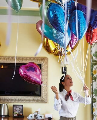 Waitress organising helium balloons in a yellow function room