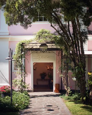 Exterior shot of a spa entrance door in a pink wall surrounded by climbing vines