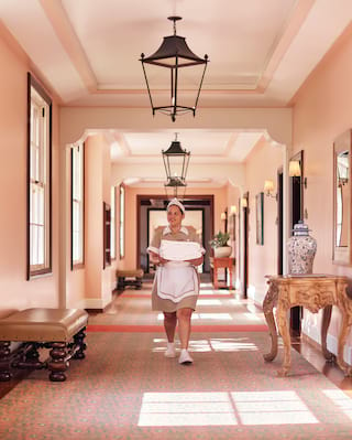 Housekeeper carrying linen along a pink sunlit corridor