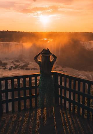 A lady admiring the Iguassu falls under an orange sunrise