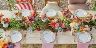 A dining table, strewn with flowers, set in the Tuscan forest