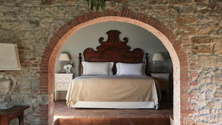 Large bed with an ornate wooden headboard, viewed through a stone-built arch