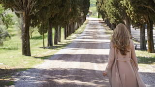 Lady walking along a driveway lined by cypress trees