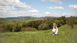 Lady in a cream poncho strolling among wild grasses overlooking the Tuscan hills