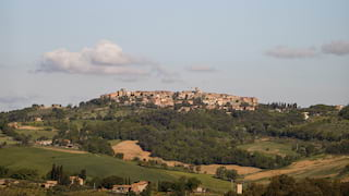 Long distance view of a stone-built village on top of a Tuscan hill