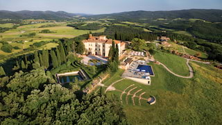 Aerial view of a sprawling castle with an outdoor pool and open-air amphitheatre