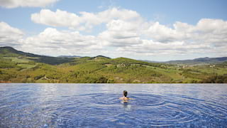Lady swimming to the edge of an outdoor infinity pool, overlooking rolling hills
