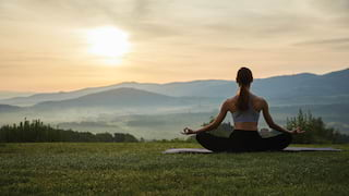 Lady in a lotus yoga pose on a lawn with views of sunrise over the Tuscan hills