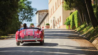 Red vintage soft-top car driving along a tree-lined driveway towards a Tuscan castle