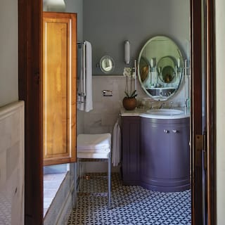 Hotel suite bathroom with a lavender-coloured sink cabinet and marble tiled wall
