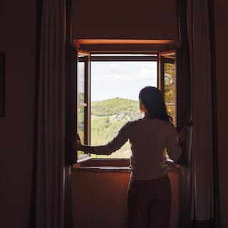 Silhouette of a lady standing at an open window gazing at the Tuscan hills