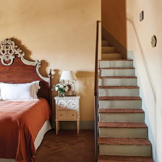 Steps leading from a peach-coloured bedroom with a terracotta bedspread