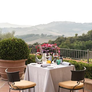 An outdoor table-for-two on a tiled restaurant terrace overlooking lush hills