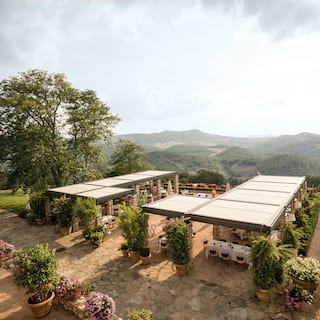 Aerial view of an outdoor dining area shaded by a pergola with hills beyond