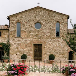 The facade of a rustic stone-built chapel with arched windows and a clay-tiled roof