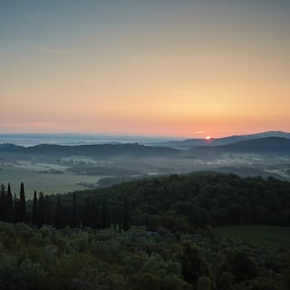 Aerial view of an orange sun rising into a clear sky above mist-coated Tuscan hills