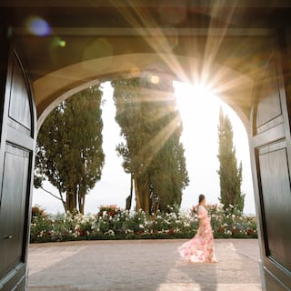 View through an arched doorway of a lady in floral dress walking by cypress trees