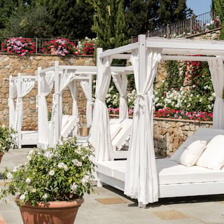 Row of pool cabanas with white drapes and cushions on a flower-coated pool patio