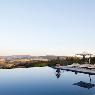 Mirror-still outdoor infinity pool overlooking Tuscan hills at sunset