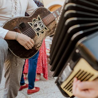 Close-up of a guitar player kneeling next to an accordion on a patio