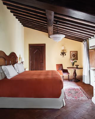 Rustic hotel room with a terracotta-coloured king bed and wooden beamed ceiling