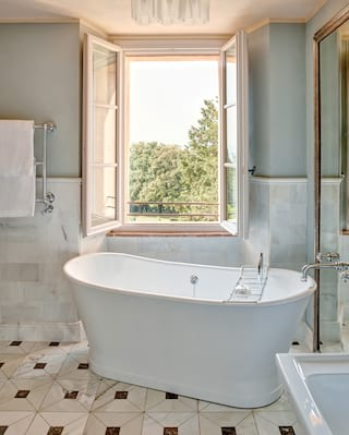 Hotel suite bathroom with a standalone bathtub next to an open window