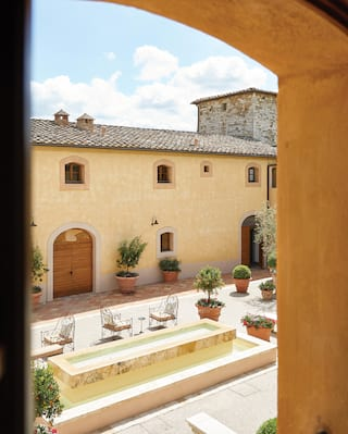 View from a window of a Tuscan castle buildings with pale yellow render