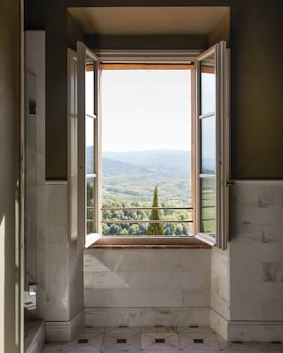 Close-up of an open picture window in a bathroom with views of the Tuscan hills