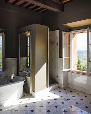 Hotel suite bathroom with open picture window casting light across marble tiles