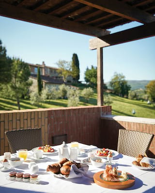 Breakfast dishes and pastries on a private balcony dining area overlooking gardens
