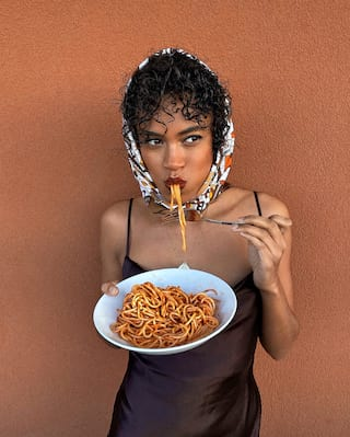 Lady wearing a colourful headscarf and eating spaghetti
