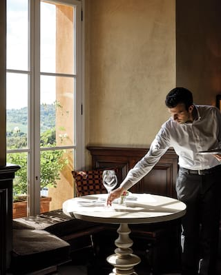 Waiter setting sparkling wine glasses on a circular table next to a window seat